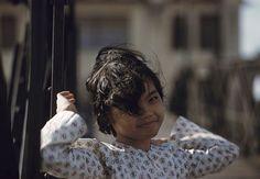 1961 - Dans le quartier chinois de Cholon, portrait en extérieur d'une fillette souriante, avec une mèche de cheveux sur un oeil, les bras levés en arrière. (Photo by Jack Garofalo/Paris Match via Getty Images)1961 - Dans le quartier chinois de Cholon, portrait en extérieur d'une fillette souriante, avec une mèche de cheveux sur un oeil, les bras levés en arrière. (Photo by Jack Garofalo/Paris Match via Getty Images)