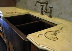 Rustic concrete countertop with a copper farm sink and iron inlay.