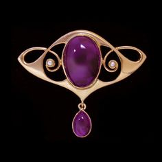 Art nouveau design.  A gold brooch set with a central cabochon amethyst and small pearls within an entrelac design mount.