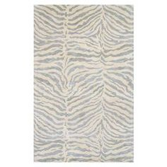 """Bring a touch of exotic appeal to your living room or master suite with this hand-tufted wool and art silk rug, showcasing a light blue and white zebra-stripe motif.  Product: RugConstruction Material: Wool and art silkColor: Light blueFeatures: Hand-tuftedPile Height: 0.5""""Note: Please be aware that actual colors may vary from those shown on your screen. Accent rugs may also not show the entire pattern that the corresponding area rugs have.Cleaning and Care: Regular vacuuming and spot ..."""