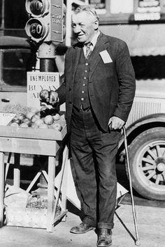 """Fred Bell, a one-time millionaire and now unemployed, sells apples at his stand on a busy street corner in San Francisco, Ca., on March 7, 1931 during the Great Depression. Bell, known as """"Champagne Fred"""" in the earlier days, has nothing left of his share of the Theresa Bell fortune as a result of the stock market crash in 1929."""