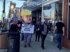"Hundreds protest Trump in April Fools' march in Ferndale. 1 April 2017. 500 in Detroit. ""I just don't think Trump is fit to be president for many reasons,"" said Susan Schneider, 61, of Temperance, wearing a yellow arm band that said ""RESIST."""