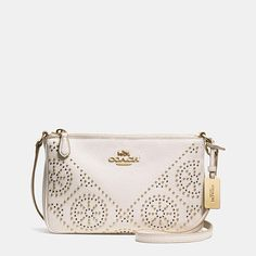Mixed-metal studs arranged in an intricate pinwheel pattern give this compact crossbody a delicate edge. Finished by hand in richly textured pebble leather, this pretty silhouette has a zippered inner pocket for valuables and a strap that adjusts for the perfect drop.