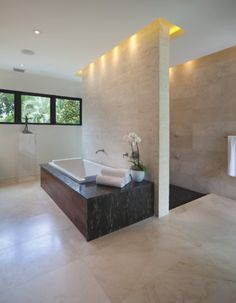 The bathtub and open shower area connect through lighting. Bet that looks great at night.