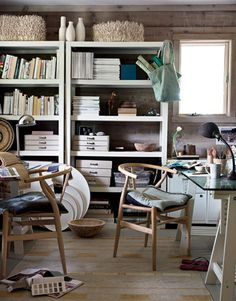 In an office the couple shares, shelves from West Elm hold beach books, stacked files, and treasures. Leaning on the floor are round bentwood trays by Canvas.   - HouseBeautiful.com