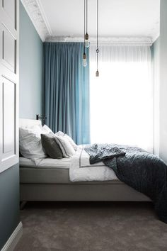 Beautiful bedroom design idea. Amazing combination of light blue curtains from floor to ceiling, grey bed, grey carpet and pendant light bulbs