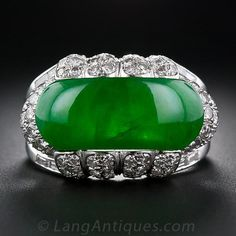 A large and impressive, deep translucent green, saddle-shapenatural-color jadeite ring. The vibrant jade saddle islavishly presented in a handmade platinum mounting with diamond-set scallops and double-tiered shoulders with shimmering baguette diamonds set down the split shank. This substantial jade saddle measures20.80 millimeters long, 8.80 mm. wideand 4.19 mm. deep. A truly stunning vintage jade ring, circa 1940s-1950s.