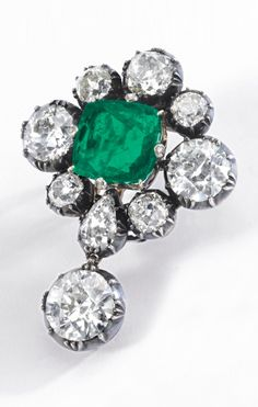 An antique emerald and diamond brooch, circa 1870. Set with a cushion-shaped emerald weighing 6.96 carats, the prongs highlighted with rose diamonds, framed with collet-set circular-cut, cushion-, and pear-shaped diamonds, supporting a circular-cut diamond drop, the reverse applied with a plaque signed G. Confalonieri Milano/Roma.