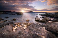 Sunset at Punta Volpe - Il maestrale Sardo con la sua forza sposta repentinamente le nuvole e prova a strozzare un timido tramonto che riesce comunque ad illuminare gli scogli di Punta Volpe. (Porto Rotondo, Sardegna)
