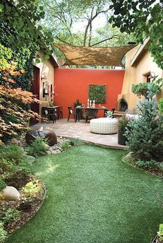 A view from the yard towards this covered courtyard between two sections f the home. The bold red accent wall against the adobe gives this space a southwestern atmosphere. Do you like the bold red? Designed by http://markdesignfirm.com/ #landscapingandoutdoorspaces