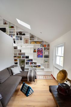 Loft Space in Camden by Craft Design | This modern apartment is a 2013 project by Craft Design that is located in Camden, London, England. It is a live-work space that has been cleverly designed to include stylish and functional shelving that covers an entire wall as well as an integrated staircase that leads to a mezzanine level.