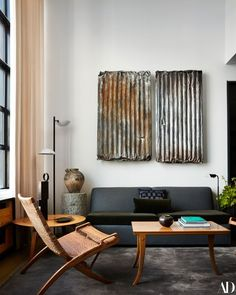 a corrugated metal sculpture hangs over a couch next to some lamps. Designed by Andre Mellone