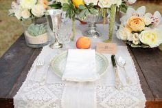Old wooden table outside on the grass with antique silver, an old-fashioned lace runner, garden roses in pale yellow and apricot hues mixed with fresh, whole fruit. Lots of other details perfecting this rustic tablescape. | Wedding Vendors (Stanleytown, VA and Durham, NC): Venue: Stoneleigh Estate / Photographer: Kellie Kano Photography / Event Design: Elissa Keno Events / Flowers: Tre Bella Florist / Wedding Invitations: Paperwhites Press / Bakery: Maxie B's Bakery
