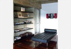 No canto do living, que era um quarto, a arquiteta aproveitou o nicho do guarda-roupa para criar a estante encaixando no concreto as prateleiras de madeira ebanizada