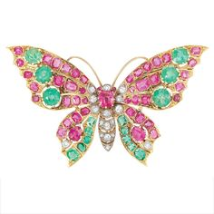 Antique Gold, Silver, Ruby, Emerald and Diamond 'en Tremblant' Butterfly Brooch  Centering one cushion-shaped ruby framed by 7 old-mine cut diamonds, atop a pierced silver diamond-set body, its pierced gold wings embellished with 16 round and cushion-shaped emeralds and 2 pear-shaped and 32 cushion-shaped rubies, accented by 2 old-mine cut diamonds, circa 1890