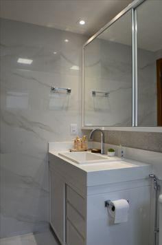 Banheiro da suíte, com marcenaria branca formando um armário com portas de correr em espelho. Bancada em nanoglass branco e cuba de sobrepor. Revestimento perolado e porcelanato imitando mármore branco.