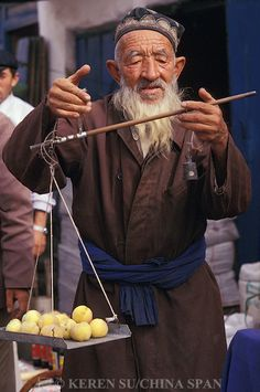 An elderly Uighur man selling fruit at Sunday market, Kashgar, Xinjiang Province, Silk Road, China