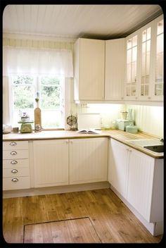 Light and crispy kitchen, under cabinet light, beadboard, wonder what that is on the floor? trap door? doorway to cellar?