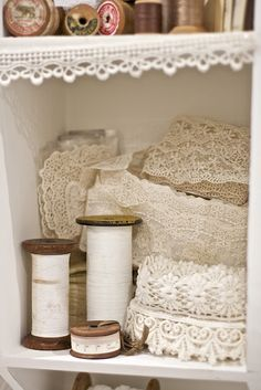 Beautiful vintage white and cream lace fills a shelf.