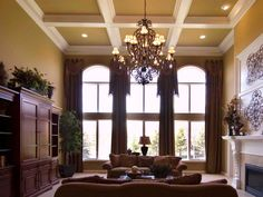 Light pours in the large arching windows of this neutral traditional living room. An elaborate chandelier suspends down from the high tray ceiling further illuminating the elegant space.