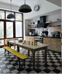Simple kitchen with checker board floor. outside box on layout with table/ bench for island. open shelving. black accents. lots of windows!
