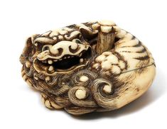 AN UNUSUAL IVORY NETSUKE OF A RECUMBENT SHISHI Late 18th century Sold for US$ 29,861 inc. premium THE HARRIET SZECHENYI SALE OF JAPANESE ART 8 Nov 2011.  Bonhams