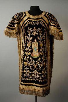 Dalmatiek van blauwzwart fluweel met zeer rijk borduursel in goud- en zilver, goudpassement en lange franjes rondom, geborduurde en geappliqueerde heilige op voor- en achterzijde | Modemuze