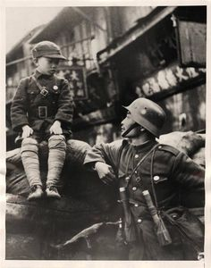 1937- Chinese soldier found time to talk to a little boy immediately before the Japanese advance drove the defenders from Nantao, Shanghai.