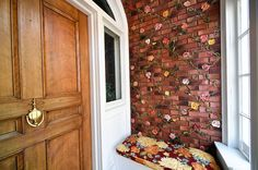 Brick wall in vestibule with floral relief and built-in bench.