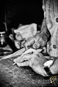 Woodmaker's Hands. A woodmaker puts the finishing touches on a hair ornament that he was making at a market.