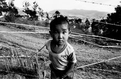 A child stands in front of the barbed wire fence that hems in the Hmong refugees living in Huay Nam Khao camp in Thailand's Phetchabun province.  © Greg Constantine