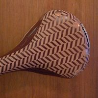 A copper-riveted brown Brooks Swift bicycle saddle which has been hand carved with a tweed herringbone pattern by American leather worker Kara Ginther into a tweed pattern. Handmade in England.