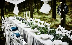 A forest wedding dining table with a white tabletop, lacycurtains as a tablecloth, white folding chairs, white tableware and a table runner centrepiece made of greenery