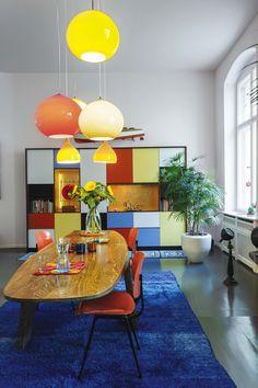Living comedor retro con aires de la década del sesenta, en tonos celeste, azul, naranja y amarillo. La mesa de madera de tres patas es obra de Gerhard Schütze.