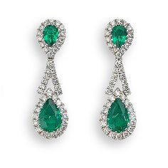 A pair of emerald and diamond drop earrings, a pair of oval cut emeralds of 0.93ct total weight, surrounded by round brilliant cut diamonds and suspended from a diamond two prong setting of 0.40ct total weight, mounted in a fine 18ct white gold setting, with post and scroll fittings.