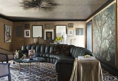 A De Sede sofa and Art Deco-style chairs surround a custom-made cocktail table in the salon; the light fixture is by Jean de Merry, and the painting at far right is by Chester Arnold.   - ELLEDecor.com