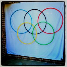 """Olympic rings for """"Olympic Birthday Party"""". Hula hoops are wrapped in Olympic colored streamers and hung with fishing wire and fish hooks on a dowel rod. We used it as a back drop for a photo booth."""