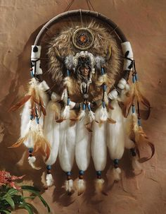 "Add a touch of rustic, Native American authenticity to your décor with this wall-hanging inspired by a warrior's dream catcher. A sculptural portrait of a warrior is suspended within a wrapped ring decorated with feathers, faux suede, faux fur and beadwork. Hangs from a brown suede cord. 13""D x 26""L. 17092"