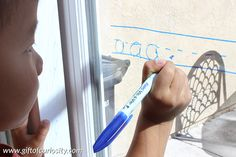 Window writing is a great way to get kids to practice their letters while also supporting the development of fine motor skills in a vertical plane. Learn about the special markers we use that make erasing the writing from the windows a breeze! || Gift of Curiosity