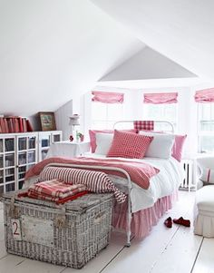 Vintage red-checked bedding from the Paris flea market echoes the red-checked window-shade fabric from Ralph Lauren in one of the guest rooms. Antique wicker hamper from Bloom. Iron bed from English Country Antiques..