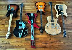 Rogues Gallery.  Lets see what we've got here; from left to right we have a Fender Telecaster, a Gretsch Duo Jet, a 'Jiminy Crickett, what on earth is that', right next to an 'Aww, thats pretty', then comes another Taylor T3 and finally an 'Is that thing upside down?'.  One of the problems with finding an uncredited photo like this is that whilst you might have an idea as to what the guitars may be, you just can't say for certain. So it's often