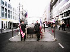 Charlie Checkpoint in Berlin. Soldiers with American flags are waiting to make photos with the tourists.