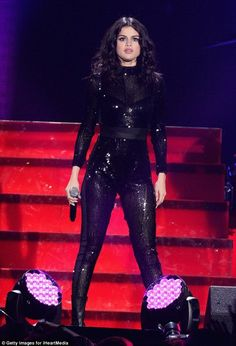 Shimmery and sheer: Selena Gomez captivated her audience on stage while clad in a skintight black bodysuit at 103.5 KISS FM's Jingle Ball 2015 in Chicago, IL on Wednesday