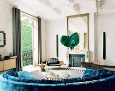 Parisian living space with round navy velvet sofa, marble fireplace, and large green plant