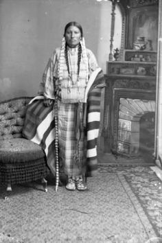 Standing studio portrait of an unidentified Native American Sioux woman wearing a plaid dress with a woven blanket, hair pipe necklace, earrings, leather belt with metal disks. Description from pinterest.com. I searched for this on bing.com/images