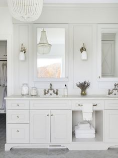 White cottage bathroom is lit by a white beaded chandelier hung over gray marble herringbone floor tiles and nickel and white glass sconces mounted beside white framed inset medicine cabinets. Grey Bathrooms, White Bathroom, Beautiful Bathrooms, Small Bathroom, Vanity Bathroom, Bathroom Ideas, Master Bathrooms, Redo Bathroom, Classic Bathroom