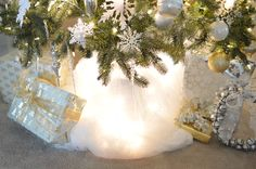 tulle tree skirt with lights - I love how the tree skirt turned out, if you can even call it that. Its just a set of those $4 tulle curtains from IKEA with Christmas lights underneath.  Easy.