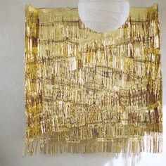 DIY Gold Fringe Photo Backdrop  Materials:  3 packs of gold fringe      Double-sided tape      ~ 5' x 6' cardboard (we used a shipping box taken apart and taped to create a flat rectangle)      Fishing line      3-4 large picture hooks from Ikea