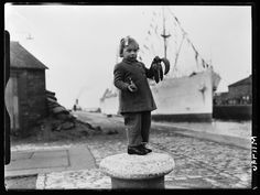 Girl standing on a bollard at Avonmouth Dock holding a bunch of bananas, taken in December 1945 by C Smith for the Daily Herald.    The photograph shows Zoya Smith holding some of the first bananas imported into Britain after the end of the second world war. This fruit came from the SS 'Tilapa', docked at Avonmouth Dock in Bristol. During the war most foodstuffs were rationed, especially those brought from overseas. Rationing in Britain officially ended in 1954.