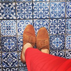 Blue and white pattern tiles. Brogues and red pants